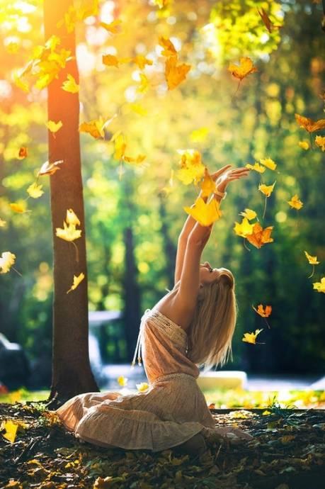 Девушка среди желтых осенних листьев