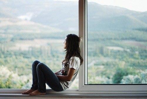 девушка в джинсах сидит на подоконнике