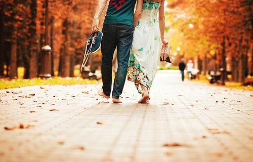 Парень с девушкой идут босиком по осенней аллее